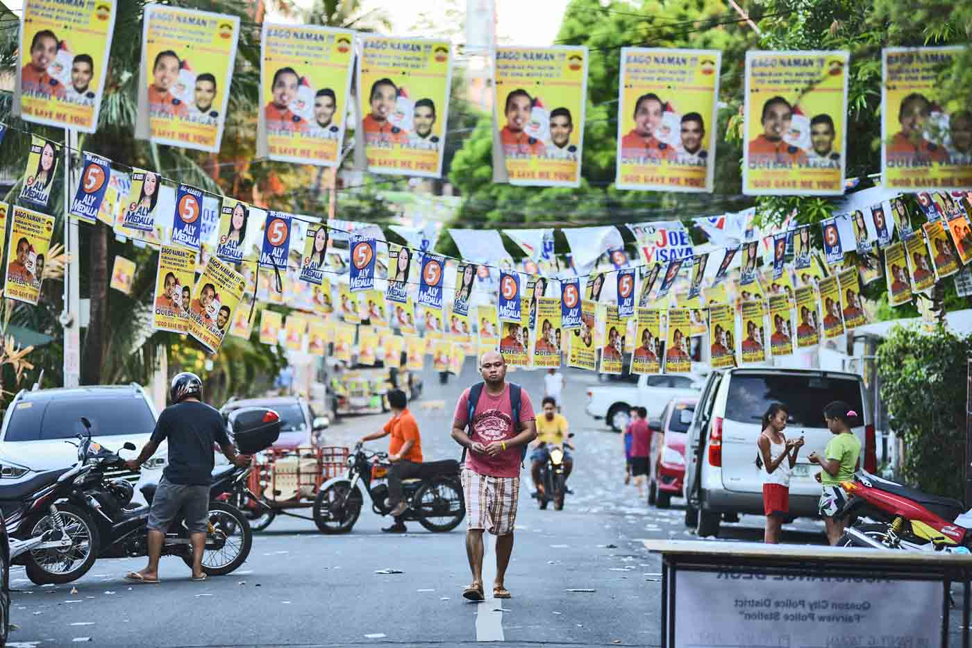 CAMPAIGN SEASON. In this file photo during the 2016 elections, a man walks past campaign banners of local politicians at Fairview in Quezon City. File photo by Martin San Diego/Rappler