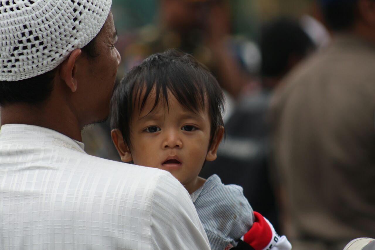 Seorang anggota FPI membawa anaknya saat berunjuk rasa di depan Mabes Polri, Senin (16/1). Foto oleh Diego Batara/Rappler