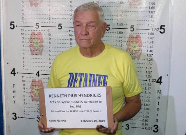 TURNED OVER. Father Kenneth Hendricks gets his mug shot taken at the Metro Manila police headquarters. NCRPO photo
