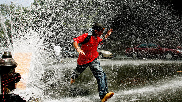 RELIEF. A young boy runs through water being sprayed by an open fire hydrant in the Bronx, New York, in this photo taken in 2006. File photo by Justin Lane/EPA
