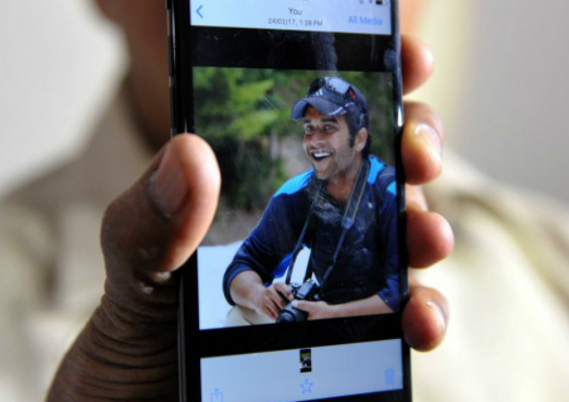 CONDEMN. Indian man Jagan Mohan Reddy holds a smartphone with an image of his son Alok Madasani at his residence in Hyderabad on February 24, 2017, after Alok was injured in a shooting in the US state of Kansas.  Photo by Noah Seelam/AFP