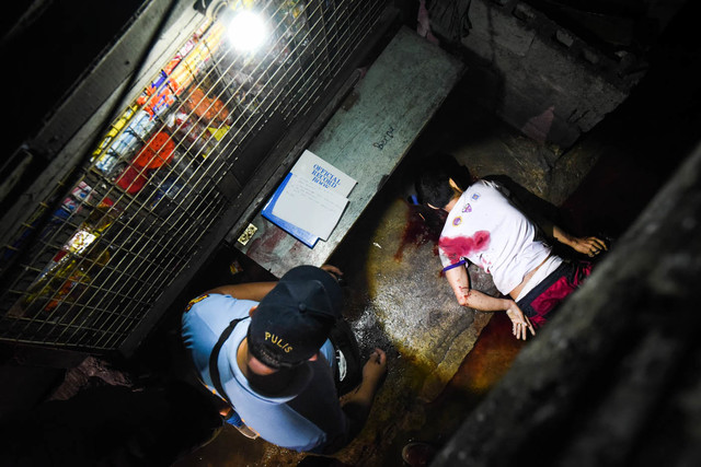DRUG WAR CASUALTY. A policeman checks a drug suspect killed in an operation. File photo by Alecs Ongcal/Rappler