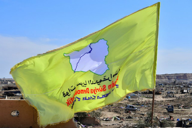 VICTORY? A picture taken on March 23, 2019 shows the US-backed Syrian Democratic Forces' (SDF) flag atop a building in the Islamic State group's last bastion in the eastern Syrian village of Baghuz after defeating the jihadist group. Photo by Giuseppe Cacace/AFP