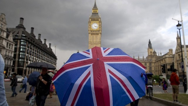 IMPASSE. File photo of a pedestrian under the rain beneath a Union flag themed umbrella walking near the Big Ben clock face and the Elizabeth Tower at the Houses of Parliament in central London. Photo by Justin Tallis/AFP
