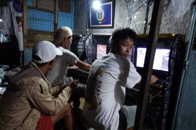 CURFEW VIOLATORS? Police stop at an outdoor computer shop in Tondo, Manila to look for minors to send home. Computer players claim they are already above 18. Photo by Rambo Talabong/Rappler
