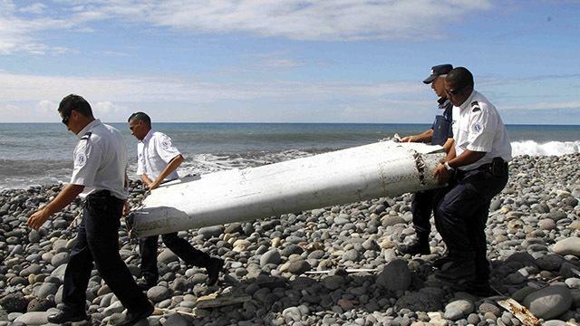 PESAWAT HILANG. Foto tanggal 30 Juli 2015 yang menunjukkan petugas tengah mengangkat puing yang diduga dari bagian pesawat dan terdampar di tepi pantai Saint-Andre de la Reunion, Perancis. Foto oleh Wae Tion/EPA