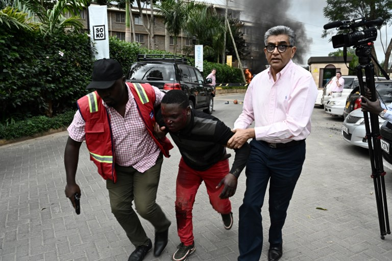 SIEGE. An injured man is evacuated from the scene of an explosion at a hotel complex in Nairobi's Westlands suburb on January 15, 2019, in Kenya. Photo by Simon Maina/AFP