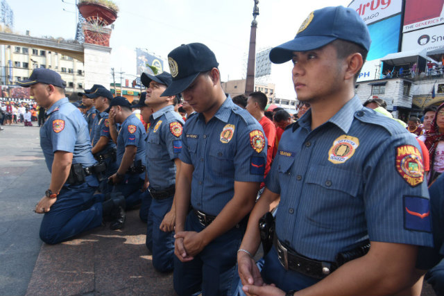 COPS AT PRAYER. Policemen join devotees in kneeling to pay homage to the Black Nazarene ahead of the annual procession of Nazareno replicas on January 7, 2018. Photo by Angie de Silva/Rappler