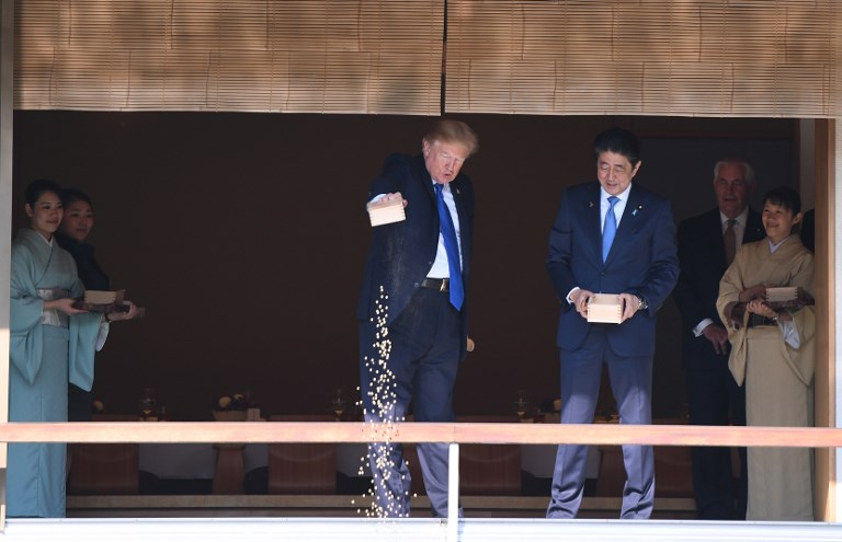 DUMP. US President Donald Trump feeds koi fish as Japanese Prime Minister Shinzo Abe looks on during a welcoming ceremony in Tokyo on November 6, 2017. Photo by Jim Watson/AFP
