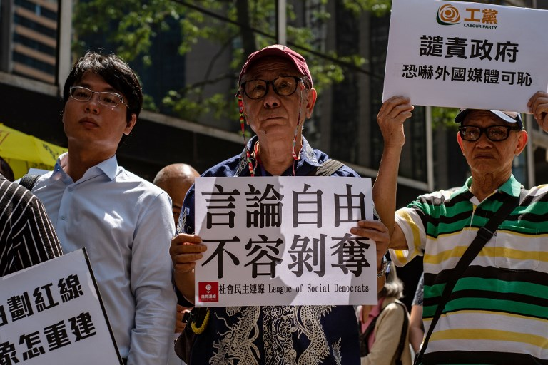 PRESS FREEDOM. A demonstrator (C) holds a placard that reads 'freedom of the press, not allowed to be deprived' during a protest after Hong Kong immigration authorities declined a visa renewal for senior Financial Times journalist Victor Mallet, outside the immigration department building in Hong Kong on October 6, 2018. File photo by Philip Fong/AFP