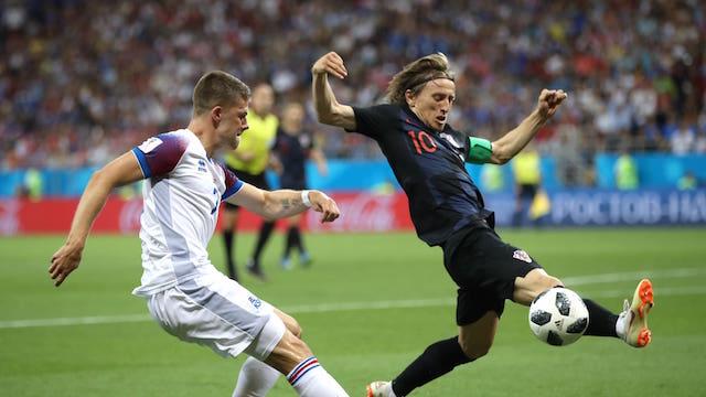 BLOK. Luka Modric dari Kroasia berusaha memblok bola dari Johann Gudmundsson dari Islandia. Foto dari FIFA.com