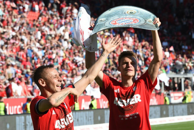 CHAMPIONS AGAIN. Bayern Munich's Brazilian defender Rafinha (L) and Bayern Munich's midfielder Joshua Kimmich (R) celebrate with a paper mock up of the Bundesliga trophy after the German first division Bundesliga football match between FC Ingolstadt 04 and FC Bayern Munich, at the Audi Sportpark in Ingolstadt, southern Germany. Photo by Christof Stache/AFP
