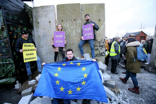 NO BORDER. A pro-EU activist holds and EU flag after protestors smashed through a mock wall, erected during a demonstration by the anti-brexit campaign group u0022Border communities against Brexitu0022 on a road crossing the border between Northern Ireland and Ireland in Newry, Northern Ireland, on January 26, 2019. Photo by Paul Faith/AFP