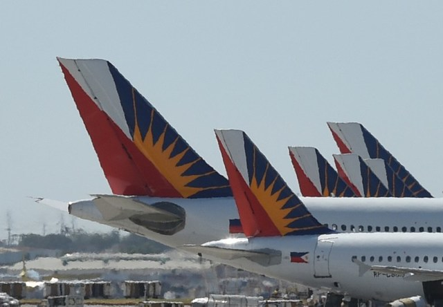 HAZY. This photo taken on January 26, 2016 shows tail sections of Philippine Airlines (PAL) aircraft while parked at the Ninoy Aquino International Airport (NAIA) Terminal 2. File photo by Ted Aljibe/AFP