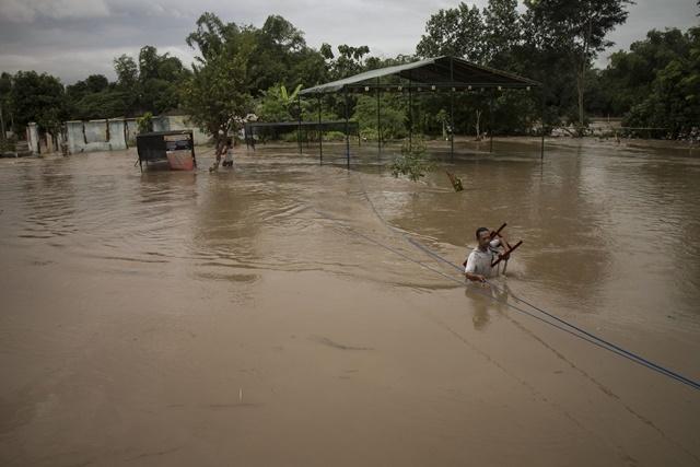 BANJIR DAN LONGSOR. Warga mengamankan perabot rumah tangga saat banjir menggenangi permukiman di Kampung Sewu, Jebres, Solo, Jawa Tengah, Minggu, 19 Juni. Foto oleh Maulana Surya/ANTARA