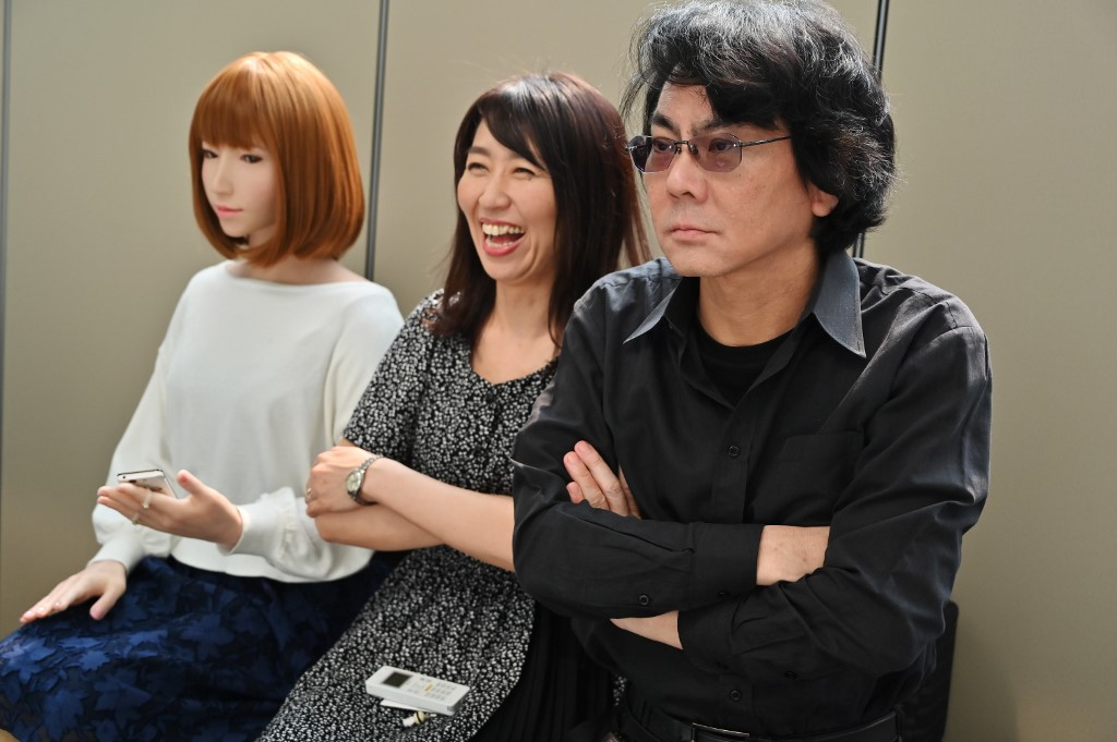ROBOTICIST. This photo taken on June 16, 2019 shows robotician Hiroshi Ishiguro (right) and his assistant (center) posing next to one of his robots at his research center in Osaka. Photo by Charly Triballeau/AFP