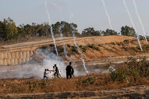 BORDER CLASHES. Palestinian protesters flee from tear gas canisters fired by Israeli forces during clashes following a demonstration along the border with Israel near Bureij in the central Gaza Strip on August 30, 2019. Photo by Mohammed Abed/AFP