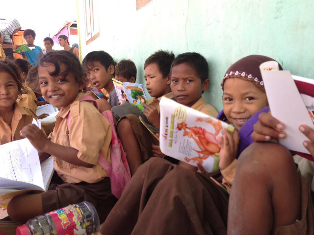 WAJAH GEMBIRA. Anak-anak di Taman Bacaan Pelangi, di Messah, NTT, antusias saat koleksi buku baru datang. All photos courtesy of Hanny Kusumawati dan Nitara Nivatvongs Layton.