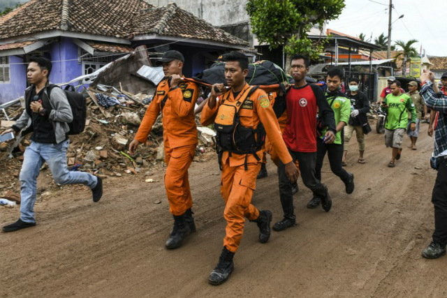 MOURNING. Members of an Indonesian search and rescue team carry the body of a victim, retrieved from a collapsed home, in a body bag in Rajabasa in Lampung province on December 25, 2018. Photo by Mohd Rasfan/AFP