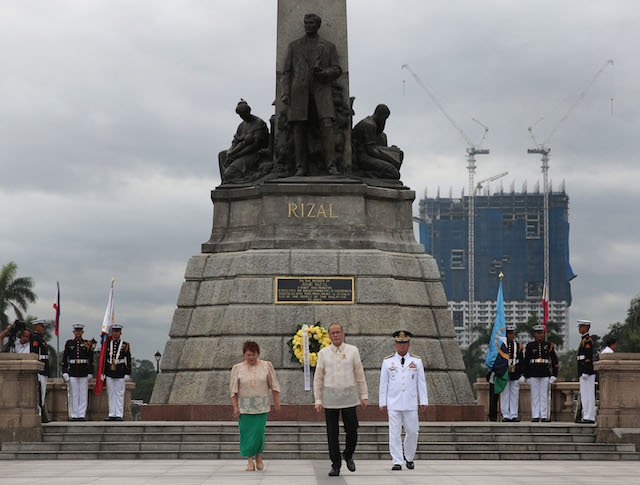 PHOTOBOMBING CONDO. President Benigno S. Aquino III leads the flag raising ceremonies for the commemoration of the 188th Anniversary of the Martyrdom of Jose Rizal at the Rizal National Monument in Rizal Park on December 30, 2014. At the back stands an unfinished condominium which as gained opposition among heritage advocates. Photo by Malacau00f1ang