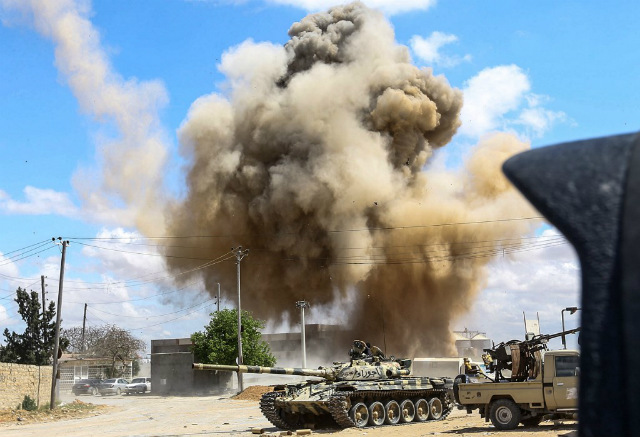 CONFLICT. This picture taken on April 12, 2019 shows a smoke plume rising from an air strike behind a tank and technicals belonging to forces loyal to Libya's Government of National Accord during clashes in the suburb of Wadi Rabie. Photo by Mahmud TURKIA / AFP