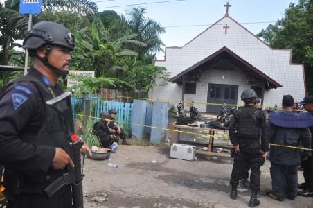 Personel Brimob Polda Kaltim mengamankan lokasi ledakan bom di Gereja Oikumene Kecamatan Loa Janan Ilir, Samarinda, Kalimantan Timur, Minggu (13/11). Foto oleh Amirulloh/ANTARA