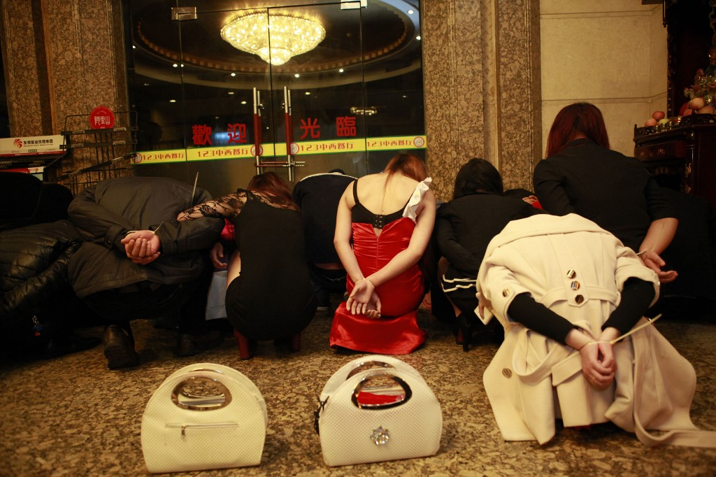 BANNED CUSTODY. This picture taken late on February 9, 2014 shows alleged sex workers and clients detained by Chinese police after a raid on an entertainment center in Dongguan, southern China's Guangdong province. Photo by STR / AFP