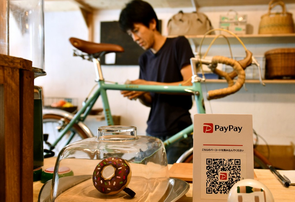 This photo taken on July 25, 2019 shows bike repair shop owner Katsuyuki Hasegawa working on a bicycle at his shop in Tokyo, next to a notice offering customers the option to settle their bill via PayPay u002du002d a tie-up between Softbank and Yahoo. Photo by Toshifumi Kitamura/AFP