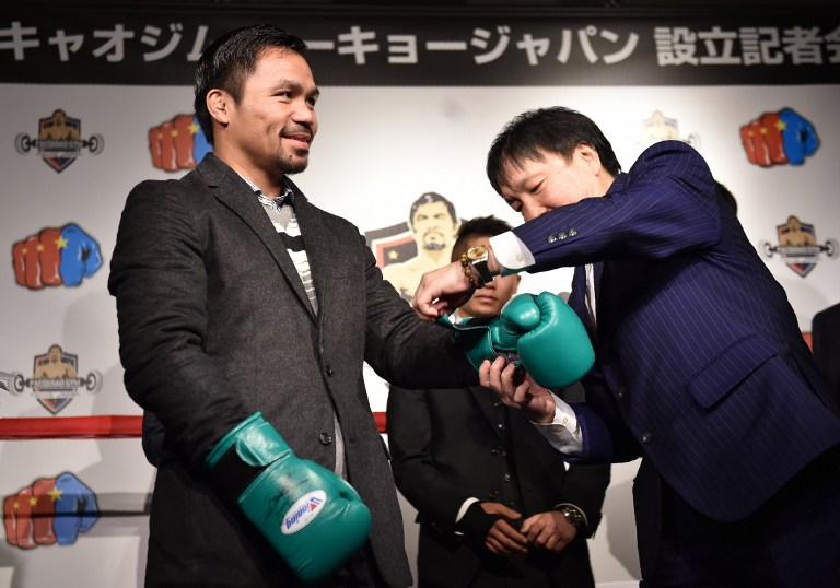OVERSEAS VENTURES. Manny Pacquiao tries on a pair of boxing gloves in Tokyo Friday, where he will open a Pacquiao Gym next year. He met with foreign reporters who were told beforehand not to ask anything related to politics. Photo by Kazuhiro Nogi/AFP