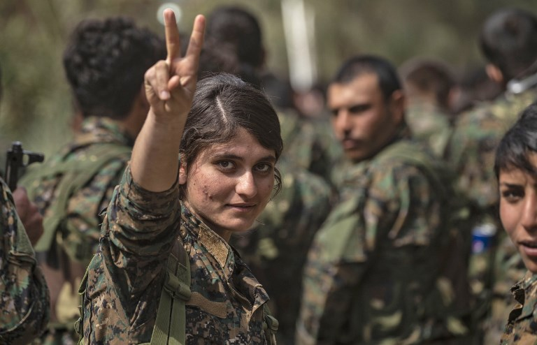 FIGHTER. A female fighter of the US-backed Kurdish-led Syrian Democratic Forces (SDF) flashes the victory gesture while celebrating near the Omar oil field in the eastern Syrian Deir Ezzor province on March 23, 2019. Photo by Delil Souleiman/AFP