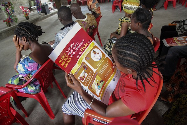 INFO DRIVE. A Liberian woman reads an Ebola information poster on the prevention of the Ebola epidemic, during UNICEF's sensitization campaign at the Mission for Today Holy Church, in Newkru Town, Monrovia, Liberia, 22 June 2014. Ahmed Jallanzo/EPA