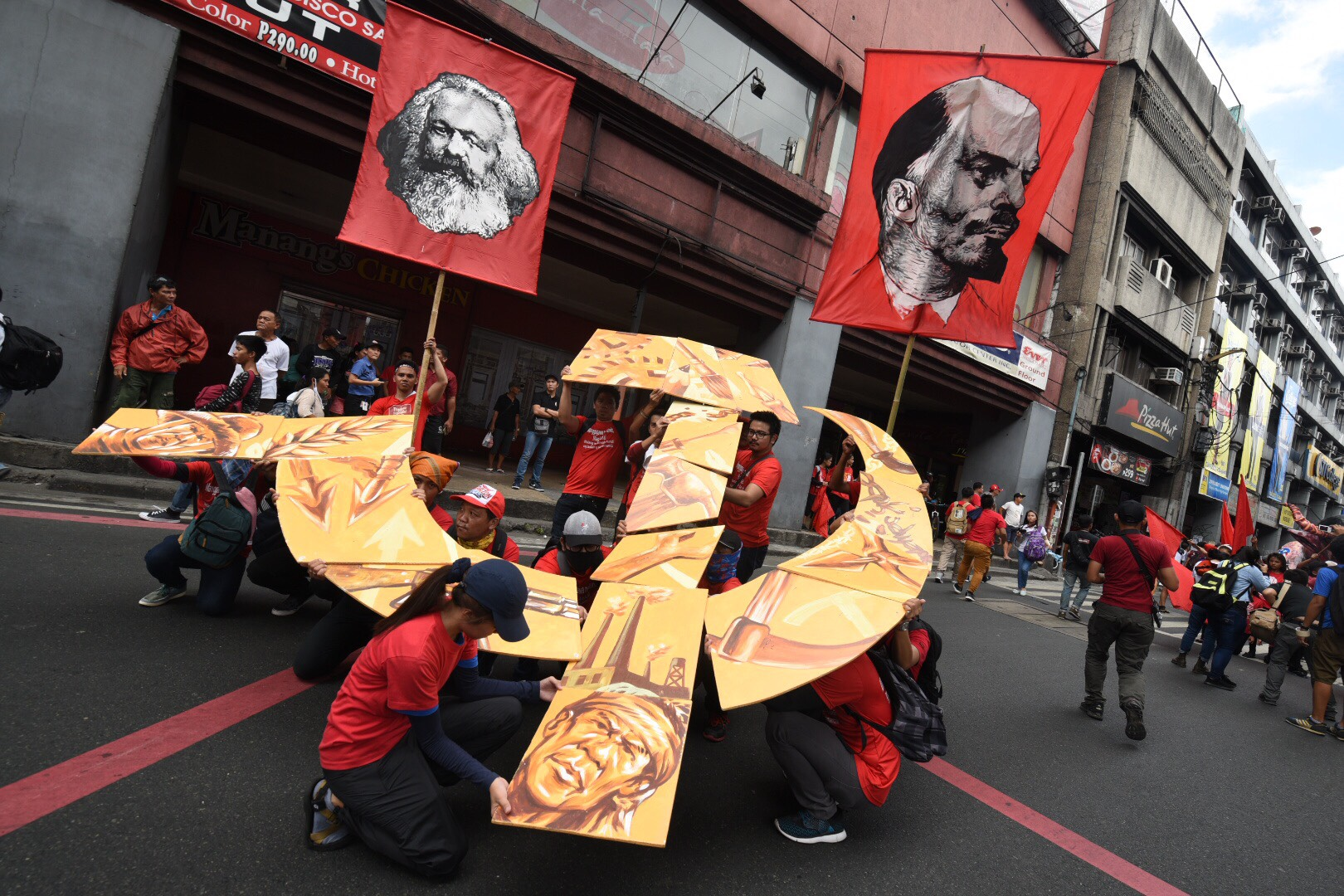 ICONS. Flags with the faces of Karl Marx and Vladimir Lenin and a stylized hammer and sickle showing faces of the Filipino marginalized are being positioned by protesters. Photo by Alecs Ongcal/Rappler