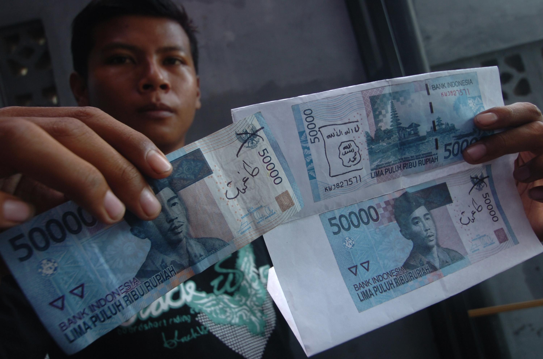 Warga menunjukkan temuan uang kertas yang dituliskan lambang ISIS di Kabupaten Ciamis, Jawa Barat, pada 27 Januari 2016. Foto oleh Adeng Bustomi/Antara