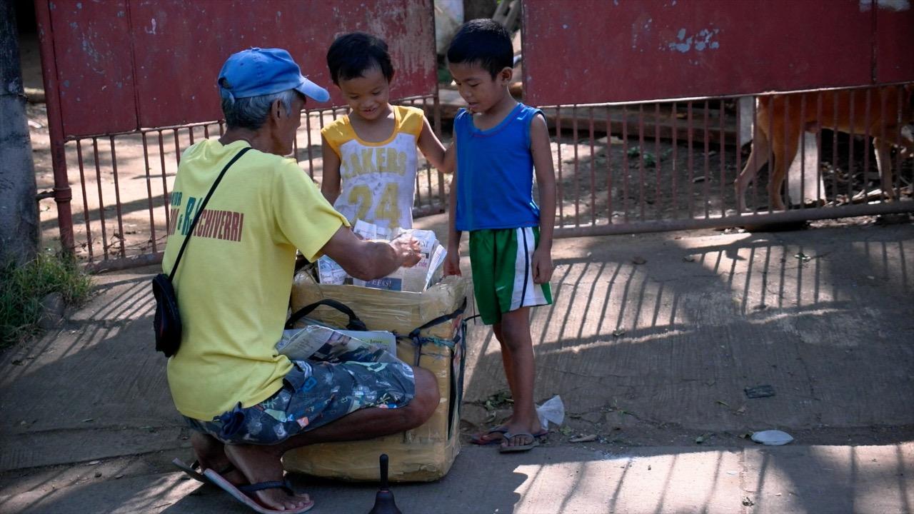 SUMMER TREAT. Arturo Fabular sells his ice drop candy to kids, going from door to door.