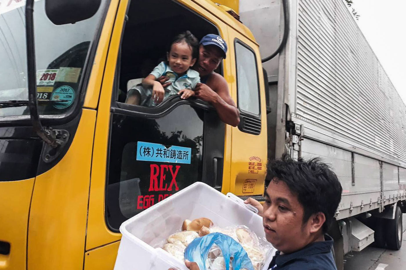 SHARING. An employee of the Land Transportation Office distributes noodles and other cooked meals to stranded motorists at the South Luzon Expressway. Photo from DOTr