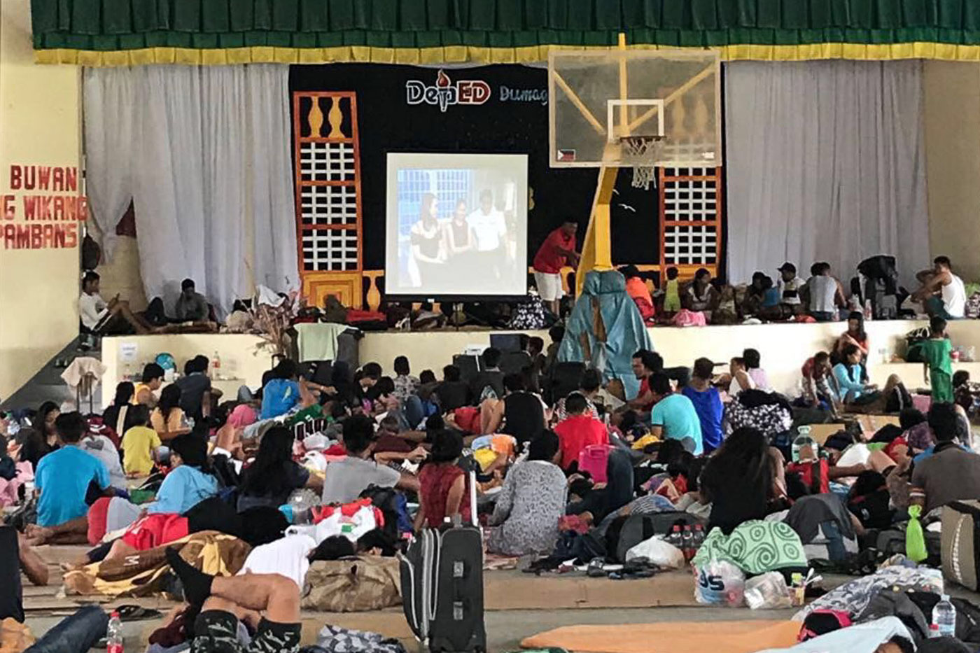 STRANDED. People at the Dumaguete City Evacuation Center watch a movie during the onslaught  of Typhoon Ompong. Photo by Jay Santiago/PPA