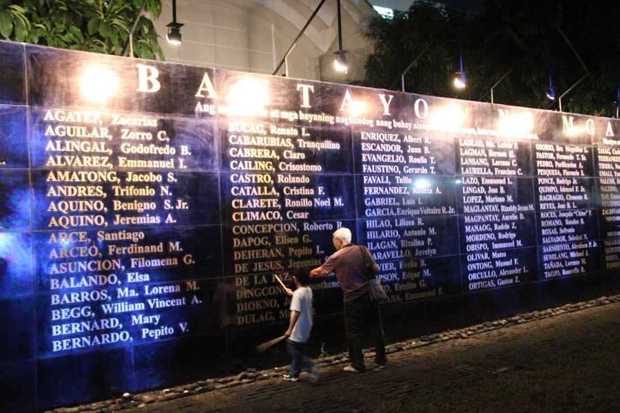 WALL OF REMEMBRANCE. An elderly man teaches a child about the significance of the Wall of Remembrance, where 268 names of martial law martyrs are inscribed in black granite. Photo by Rome Jorge/Rappler