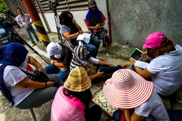 CAREFUL SUPPORT. Iglesia Ni Cristo members converge at 36 Tandang Sora to support Angel and Tenny Manalo on July 26. Some of the members cover their faces to hide their identities and avoid expulsion. Photo by Mark Saludes/Rappler
