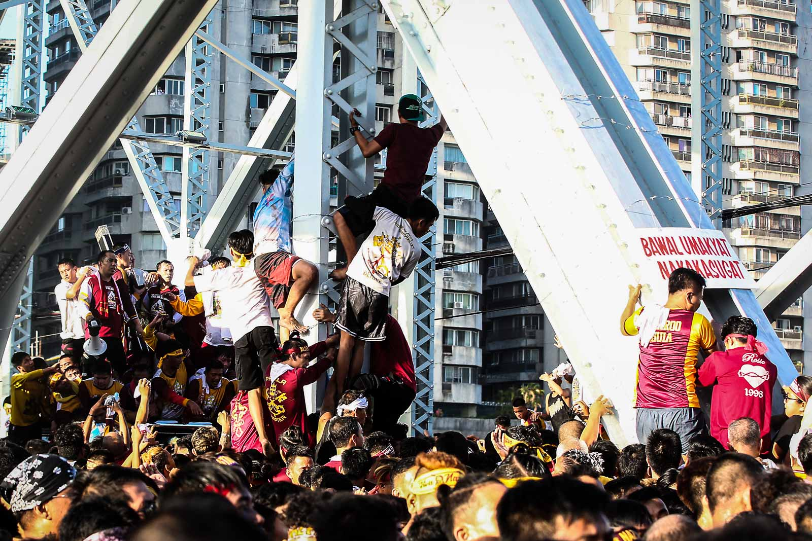 Devotees climb into the Ayala bridge to get a glimpse of the image of the Black Nazarene during the Traslacion on January 9, 2020. Photo by Ben Nabong/Rappler