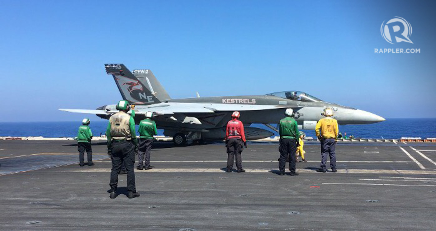 CREW. Color-coded crew prepare for the takeoff of a fighter jet. According to the US Navy, the aircraft carrier strike group has 5,000 crew, 16% of them female. Photo by Camille Elemia/Rappler