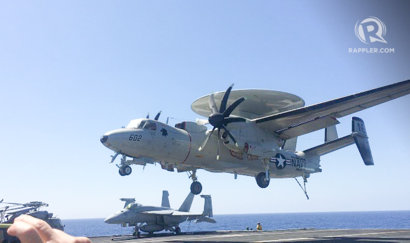HAWKEYE. A US Navy E-2C Hawkeye, an early warning and command and control aircraft, about to land, as Philippine officials and media look on. Photo by Camille Elemia/Rappler