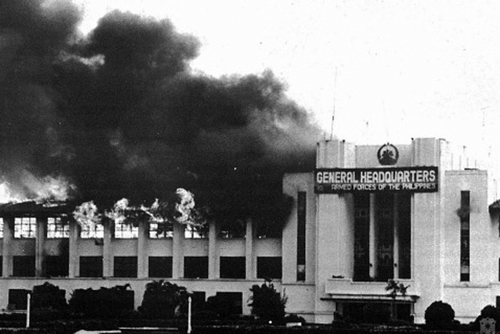 AUGUST 1987 COUP. The headquarters of the Armed Forces of the Philippines in Camp Aguinaldo is bombed by rebel soldiers. Photo courtesy of Malacau00f1ang
