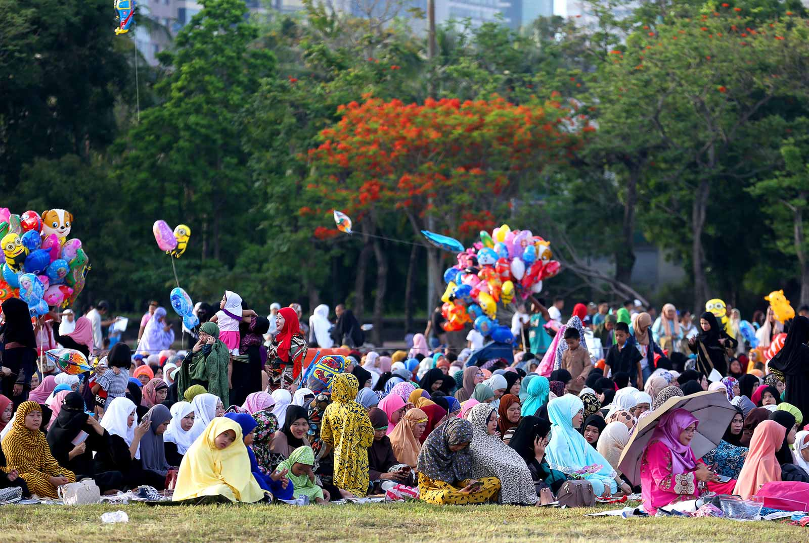 CELEBRATION. Muslim women of Marawi City give each other a hug after the Eid prayers (above) while families spend the rest of the morning at the Luneta Park in Manila. Photos by Martin San Diego and Inoue Jaena/Rappler