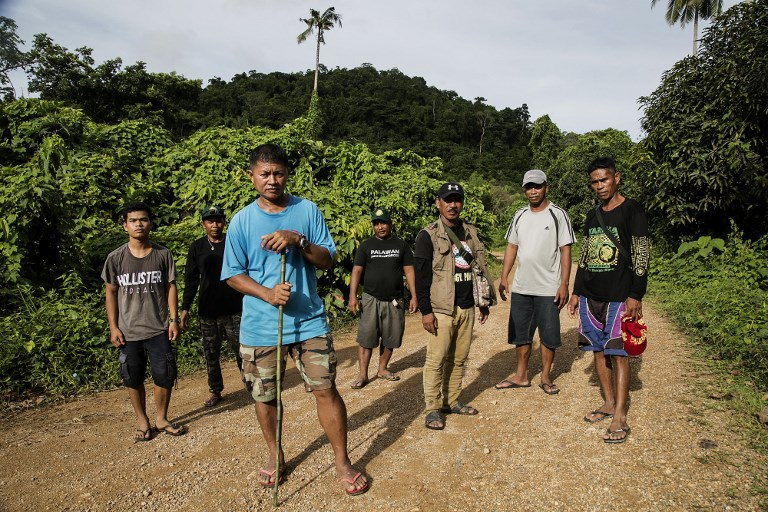 ENVIRONMENTAL CRUSADE. This photo taken on September 26, 2017, shows Efren 'Tata' Balladares (3rd-L), one of the leaders of the Palawan NGO Network Inc (PNNI), standing in front of other para-enforcers from the group on the outskirts of a forest near the tourist town of El Nido, on Palawan island in the Philippines. Karl Malakunas/AFP