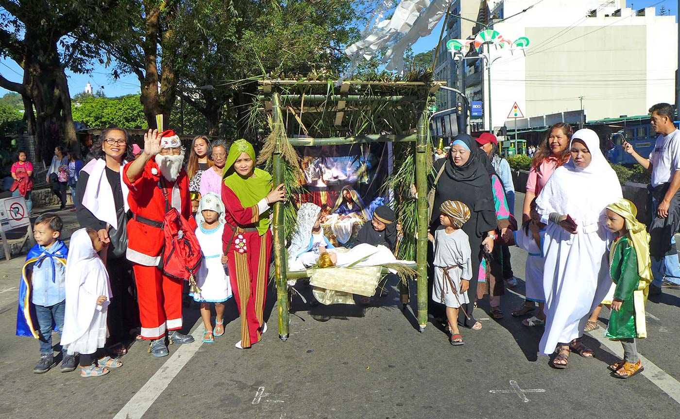 CHRIST IS BORN. The parade also includes kids and parents reenacting the birth of Jesus in a manger