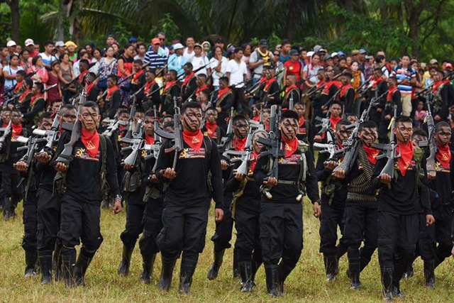 TALKING WHILE FIGHTING? Communist rebels in their recent anniversary celebration. File photo by Rappler