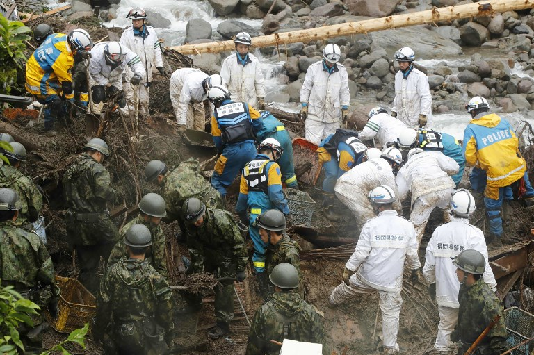 Japanese policemen and members of Self-Defence Forces (SDF) take part in search operations for missing people at flood area in Toho village, Fukuoka prefecture on July 7, 2017. Photo by Jiji Press/AFP