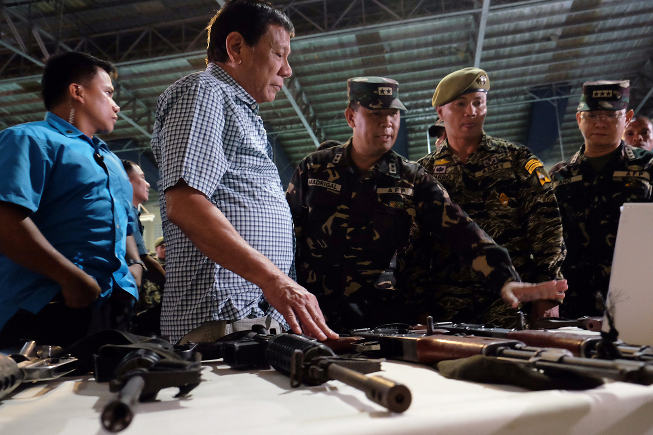 NPA GUNS. President Rodrigo Duterte checks the firearms recovered from the New People's Army rebels during his visit at Camp Edilberto Evangelista in Patag, Cagayan de Oro City on August 9, 2016. Malacau00f1ang file photo