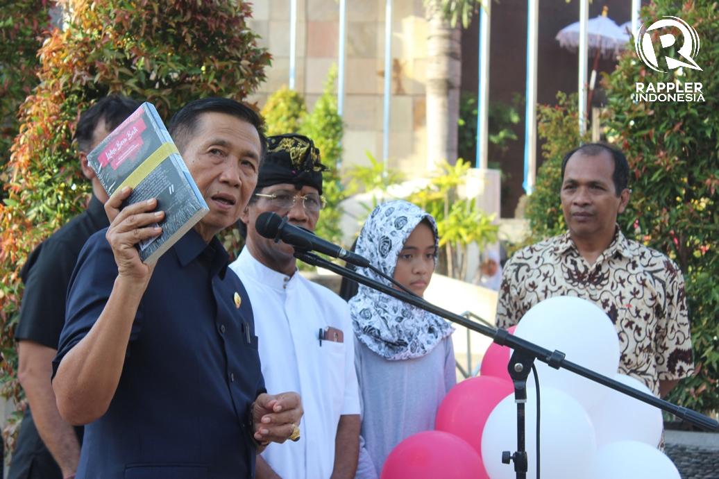 BUKU. Gubernur Bali Made Mangku Pastika saat menunjukkan buku berjudul Luka Bom Bali. Foto oleh Bram Setiawan/Rappler