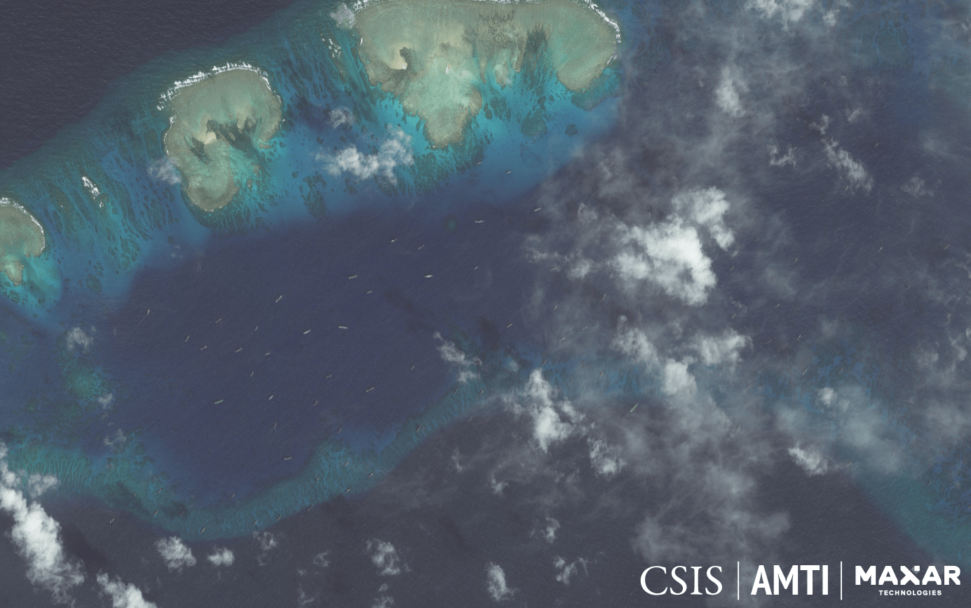 THE SWARM. The tiny specks on the water's surface in this satellite image are Chinese fishing boats whose constant, idle presence among the sandbars just off Pag-asa Island lead analysts to conclude they are militias. Photo from AMTI-CSIS